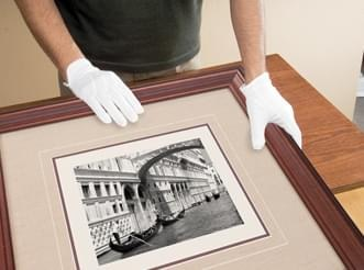 Specialist wearing white gloves performs a final check of framed artwork